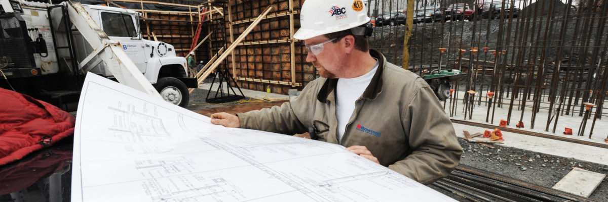 photo of worker looking over design plans at construction site