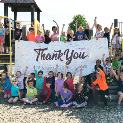 photo of caribou community school students with signed thank you banner at playground