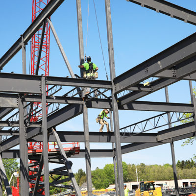 photo of workers on roof at construction site at caribou community school beam signing ceremony