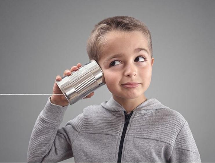 photo of child holding a can on a string to his ear
