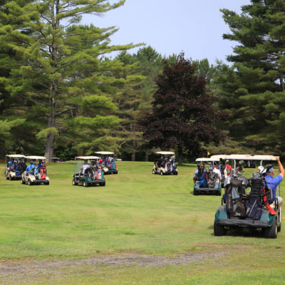 photo of full golf carts on the green at sebasticook valley FCU golf tournament