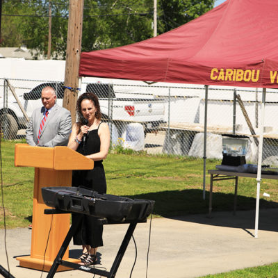 photo of kim barnes speaking at caribou community school beam signing ceremony
