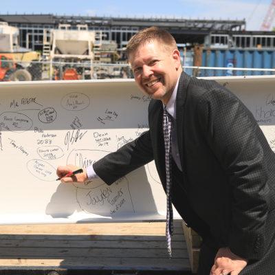 photo of school principal signing beam