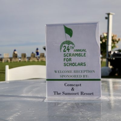 photo of sign on table 24th annual scramble for scholars welcome reception sponsored by comcast and the samoset resort