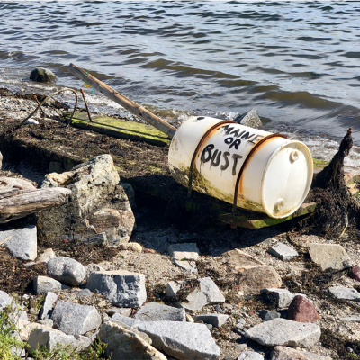 "photo of a plastic barrel with the words ""Maine or Bust"" drawn on it"
